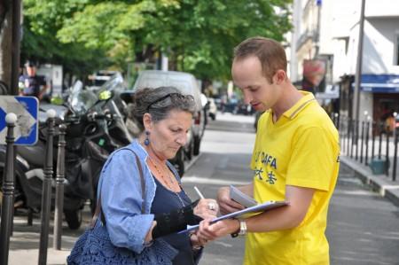 商人Marie-Christine女士簽完名後心情沉重地說:「我們法國人世代都在追求人權、自由和博愛,全世界都知道。但是在中國,還在酷刑折磨人。」(金湖/大紀元)