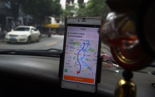 2016年5月,廣西桂林一名出租車司機在使用滴滴出行軟件。(AFP / GREG BAKER        (Photo credit should read GREG BAKER/AFP/Getty Images)
