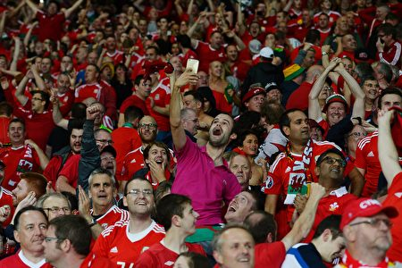 Wales supporters celebrate at the end of the Euro 2016 quarter-final football match between Wales and Belgium at the Pierre-Mauroy stadium in Villeneuve-d'Ascq near Lille, on July 1, 2016. / AFP / MIGUEL MEDINA (Photo credit should read MIGUEL MEDINA/AFP/Getty Images)
