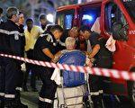法国14日庆祝国庆,南部尼斯市(Nice)民众在观赏烟火秀后,离开现场时,1辆卡车突然冲入人群,已造成至少84人丧生,约200人受伤,52人生命垂危。图为救援人员将伤者送入救护车。(VALERY HACHE/AFP/Getty Images)