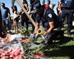 7月16日(週六),一名法國警察在尼斯恐襲現場放置鮮花,悼念遇難者。17日警方又逮捕兩名嫌犯,使尼斯恐怖襲擊案被捕人數增至7人。(Carl Court/Getty Images)