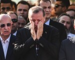 """TOPSHOT - EDITORS NOTE: Graphic content / Turkey's President Recep Tayyip Erdogan (C) reacts after attending the funeral of a victim of the coup attempt in Istanbul on July 17, 2016.  Turkish President Recep Tayyip Erdogan vowed today to purge the """"virus"""" within state bodies, during a speech at the funeral of victims killed during the coup bid he blames on his enemy Fethullah Gulen. / AFP / BULENT KILIC / The erroneous mention[s] appearing in the metadata of this photo by BULENT KILIC has been modified in AFP systems in the following manner: [unknown individuals] instead of [police officers]. Please immediately remove the erroneous mention[s] from all your online services and delete it (them) from your servers. If you have been authorized by AFP to distribute it (them) to third parties, please ensure that the same actions are carried out by them. Failure to promptly comply with these instructions will entail liability on your part for any continued or post notification usage. Therefore we thank you very much for all your attention and prompt action. We are sorry for the inconvenience this notification may cause and remain at your disposal for any further information you may require.        (Photo credit should read BULENT KILIC/AFP/Getty Images)"""