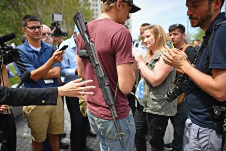 带枪的民众和记者交谈。(Jeff Mitchell/Getty Images)