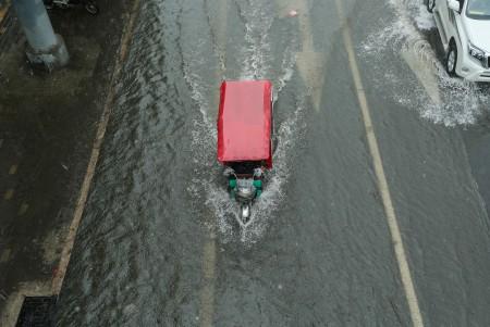 7月20日北京暴雨。图为一辆三轮车在积水中艰难前行。 (STR/AFP/Getty Images)