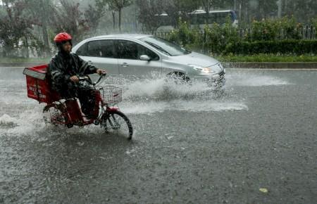 7月20日北京街头,暴雨中的摩托车和汽车。(STR/AFP/Getty Images)