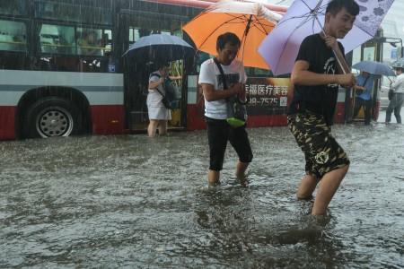 7月20日北京暴雨。图为北京路上行人。(STR/AFP/Getty Images)