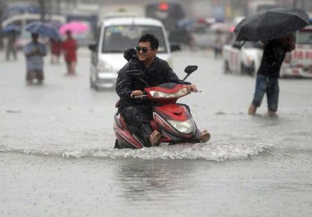 7月20日北京街头,一个男子开车摩托车涉水前行。(STR/AFP/Getty Images)