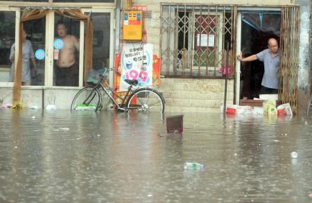 7月20日,北京居民看着屋外的洪水。(STR/AFP/Getty Images)