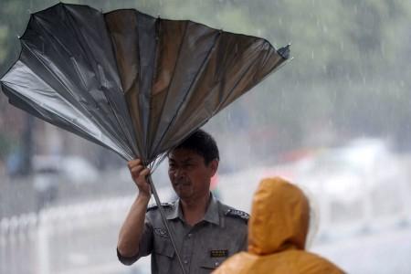 7月20日,北京男子走在街頭,傘被狂風吹翻。暴雨造成至少1死34傷。 (STR/AFP/Getty Images)