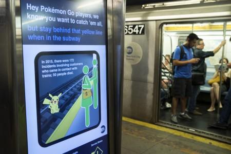 圖為7月20日紐約地鐵出示電子看板警告Pokemon Go玩家注意搭地鐵安全。(Drew Angerer/Getty Images)