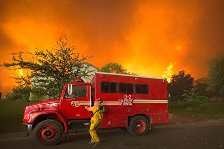 消防隊員在受砂火威脅的民宅前。(DAVID MCNEW/AFP/Getty Images)