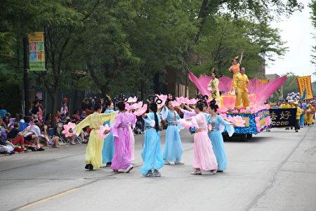 法轮功队伍中,身着彩衣、手持莲花的仙女们翩翩起舞。(王松林/大纪元)