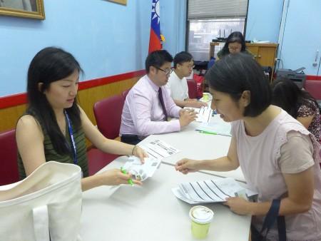 鄺女士(右)在記者會後就填表參加篩檢。