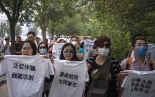 中国大陆泛亚公司去年4月停止支付本金及收益后,血本无归的投资者在地方政府及远赴北京多次抗议,但反而遭到逮捕及打压。图为去年9月到北京抗议的泛亚投资人。(FRED DUFOUR/AFP/Getty Images)
