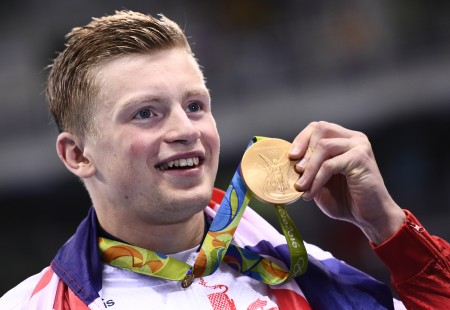 Britain's Adam Peaty poses on the podium with his gold medal after he broke the World Record in the Men's 100m Breaststroke Final during the swimming event at the Rio 2016 Olympic Games at the Olympic Aquatics Stadium in Rio de Janeiro on August 7, 2016. / AFP PHOTO / Martin BUREAU