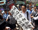 昨日一批愛字頭成員到民主黨總部示威,林卓廷手持「民建聯最無恥、撐CY損廉潔」標語到場反擊。(李逸/大紀元)