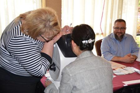 參加西雅圖華人健康展的「美國最好眼鏡及隱形眼鏡」公司為民眾測試視力。(舜華/大紀元)