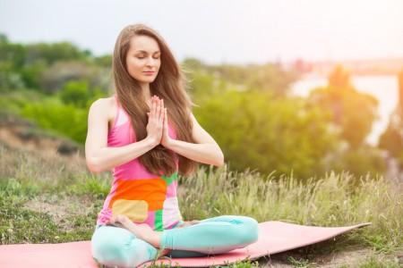 Pretty woman doing yoga exercises on nature landscape