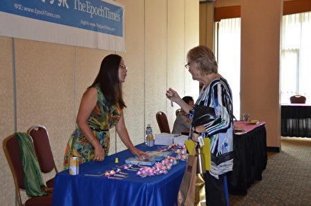 金郡衛生署主任Patty Hayes女士在法輪大法的攤位饒有興趣聽取關於法輪功可以帶來身心健康的介紹。(舜華/大紀元)