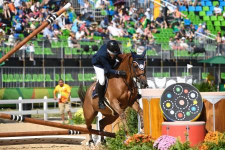 """台湾首位""""骑""""进奥运的女骑手汪亦岫在障碍马术赛中,因马匹莎莎不适应高温,在第13个障碍挑战失败后选择弃赛。(AFP)"""