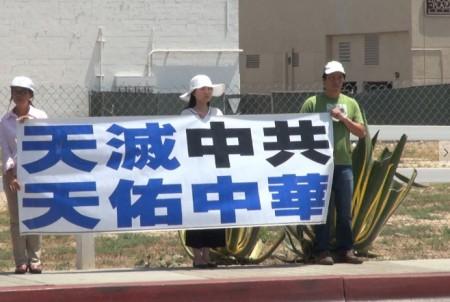 法輪功學員們在酷暑的豔陽下靜靜地舉著展板表達他們的訴求。(薛文/大紀元)