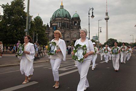 7月30日,法輪功學員在柏林舉行大型遊行活動。圖為身穿白色衣褲的學員手捧被迫害致死的學員的照片走過柏林大街。(Jason Wang/大紀元)