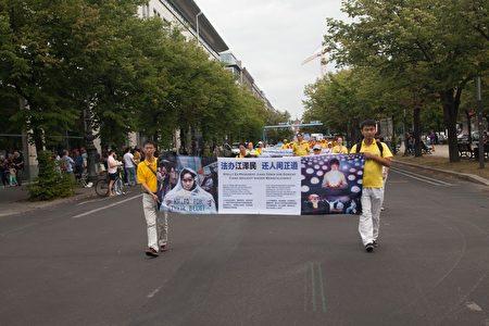 7月30日,法輪功學員在柏林舉行的大型遊行活動,圖為法輪功學員打出橫幅,揭露迫害。(Jason Wang/大紀元)