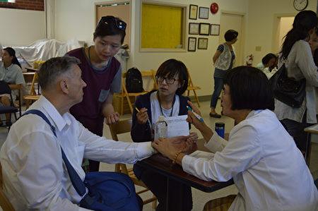 杨素卿中医师率领台湾中医服务队抵温义诊,图为她现场为西人义诊。(邱晨/大纪元)