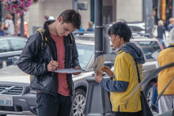 西雅图法轮功学员征签传真相  各地游客支持