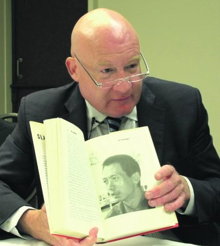 8月16日,葛特曼在纽西兰惠灵顿接受大纪元专访。图为他向记者展示他的著作《大屠杀》。(视频截图/大纪元)