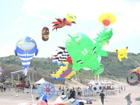 新北市北海岸國際風箏節24日邀世界各國風箏好手齊聚石門白沙灣競技及炫目展演,選手帶來各具代表的風箏,將湛藍的天空妝點得熱鬧非凡。許多遊客看到大型風箏,直呼太漂亮了。(新北市政府提供)