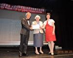 纽约州参议员史塔文斯基(中)向台湾桃园市纯青合唱团颁发褒奖,表扬他们为承传和弘扬客家文化所作的努力。左一为团长黄崇茂,右一为大纽约客家会会长杨毓淑。 (林丹/大纪元)