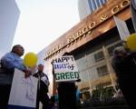 圖為2011年10月,抗議華爾街者在洛杉磯市內一家富國銀行分行前舉牌,牌上寫道:為160年的貪婪史慶生。(David McNew/Getty Images)