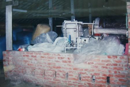 草创时期在猪舍中所安装的羽绒填充机。(赖友容/大纪元)