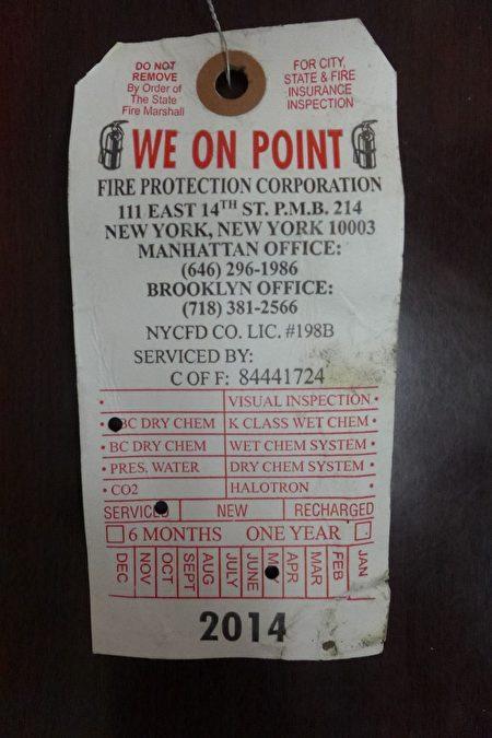 两人拿着一个白色的过期吊牌(年检时间显示2014年5月)偷梁换柱,以此要挟邓学源交钱。