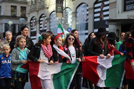 游行队伍中手拿意大利国旗的孩子们。