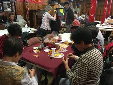 华人老阿姨在编手工艺品。