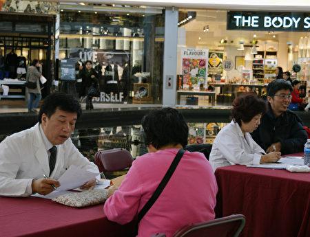 图:加拿大国家中医药学会在Aberdeen购物中心举办义诊,图为王炯峰医师在义诊。(邱晨/大纪元)