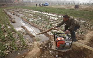 "This photo taken on February 8, 2011 shows a Chinese farmer watering his drought-stricken wheat field in Luoyang, north China's Henan province, as the worst drought in six decades affecting large swathes of northern China. China called for higher rice output to offset damage to its wheat crop in the drought-stricken north and pledged $1 billion in spending to battle a problem the UN warned could be ""very serious"".  CHINA OUT AFP PHOTO (Photo credit should read STR/AFP/Getty Images)"