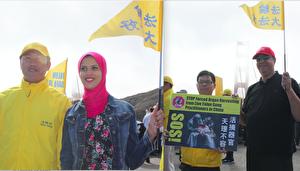 来自埃及的一对医生夫妇和他们的女儿主动要求跟澳洲法轮功学员合影并挥舞法轮大法好的小旗子。(骆亚/大纪元)