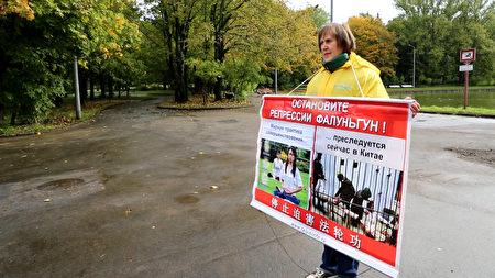 俄羅斯法輪功學員塔蒂亞娜在莫斯科中使館前舉牌抗議中共非法迫害法輪功。(新唐人)