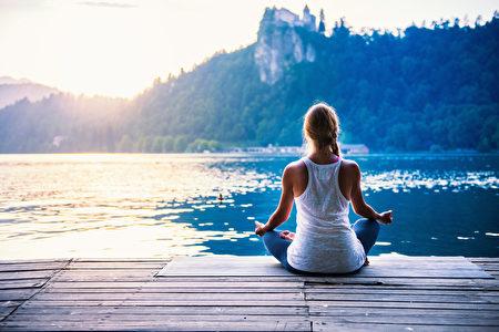 瑜伽莲花。年轻女子在湖边做瑜伽,坐在莲花。(fotolia)