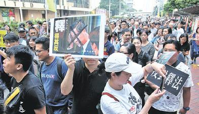 1.3萬人昨日遊行抗議中共人大釋法,不少遊行人士直指事件的元凶是特首梁振英和背後的江派人大委員長張德江。( 潘在殊/大紀元)