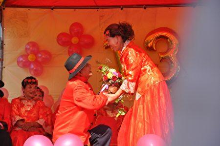 78岁村长新郎庄明洲特别兴奋,很大方的在台上向老伴邱红甘求婚,还大方亲吻新娘,博得现场掌声喝采。(詹亦菱/大纪元)
