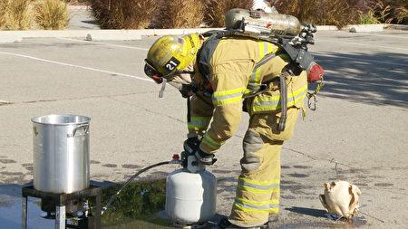 消防員將火撲滅檢查設備。(楊陽/大紀元)