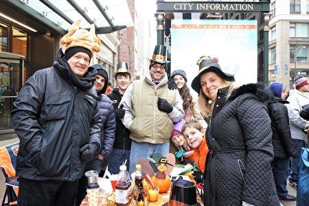 Kevin Kraujalis(左)一家人11口一大早就帶上早餐、咖啡,擺上桌子邊看遊行邊慶祝節日。 (溫文清/大紀元)