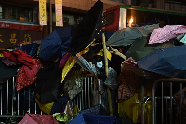 Demonstrators protect themselves with umbrellas during a stand-off with police during ongoing protests in Hong Kong on November 6, 2016. Hong Kong police used pepper spray November 6 to drive back hundreds of protesters angry at China's decision to intervene in a row over whether two pro-independence lawmakers should be barred from the city's legislature. In chaotic scenes reminiscent of mass pro-democracy protests in 2014, demonstrators charged metal fences set up by police outside China's liaison office in the semi-autonomous city. / AFP / Anthony WALLACE (Photo credit should read ANTHONY WALLACE/AFP/Getty Images)