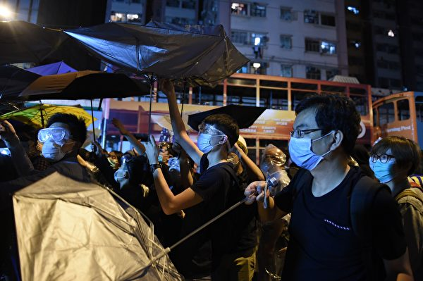 Demonstrators carry umbrellas during a stand-off with police during ongoing protests in Hong Kong on November 6, 2016. Hong Kong police used pepper spray November 6 to drive back hundreds of protesters angry at China's decision to intervene in a row over whether two pro-independence lawmakers should be barred from the city's legislature. In chaotic scenes reminiscent of mass pro-democracy protests in 2014, demonstrators charged metal fences set up by police outside China's liaison office in the semi-autonomous city. / AFP / Anthony WALLACE (Photo credit should read ANTHONY WALLACE/AFP/Getty Images)