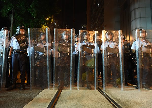 Police stand guard during a stand-off with demonstrators amid ongoing protests in Hong Kong on November 6, 2016. Hong Kong police used pepper spray November 6 to drive back hundreds of protesters angry at China's decision to intervene in a row over whether two pro-independence lawmakers should be barred from the city's legislature. In chaotic scenes reminiscent of mass pro-democracy protests in 2014, demonstrators charged metal fences set up by police outside China's liaison office in the semi-autonomous city. / AFP / Anthony WALLACE (Photo credit should read ANTHONY WALLACE/AFP/Getty Images)
