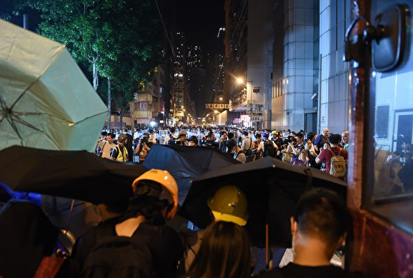 Police stand beyond a line of protesters (foreground) as they block off a street amid ongoing protests in Hong Kong on November 6, 2016. Hong Kong police used pepper spray November 6 to drive back hundreds of protesters angry at China's decision to intervene in a row over whether two pro-independence lawmakers should be barred from the city's legislature. In chaotic scenes reminiscent of mass pro-democracy protests in 2014, demonstrators charged metal fences set up by police outside China's liaison office in the semi-autonomous city. / AFP / Anthony WALLACE (Photo credit should read ANTHONY WALLACE/AFP/Getty Images)